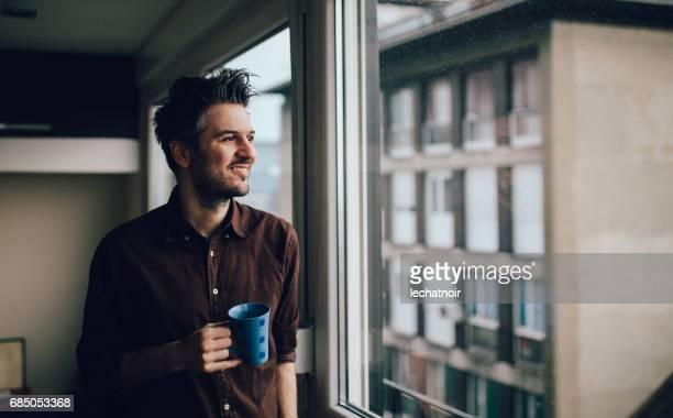 Junger Mann, Kaffeetrinken in der Wohnung