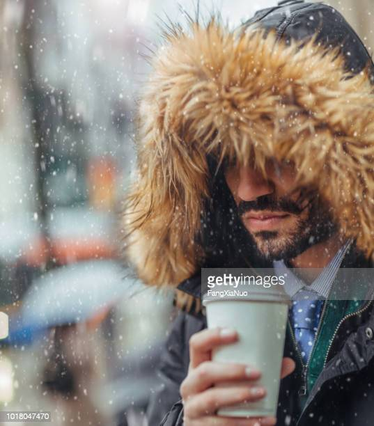 young man drinking coffee on city street on a snowy day - winter coat stock pictures, royalty-free photos & images