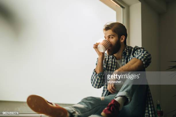 young man drinking coffee while relaxing on a window sill. - coffee break stock pictures, royalty-free photos & images