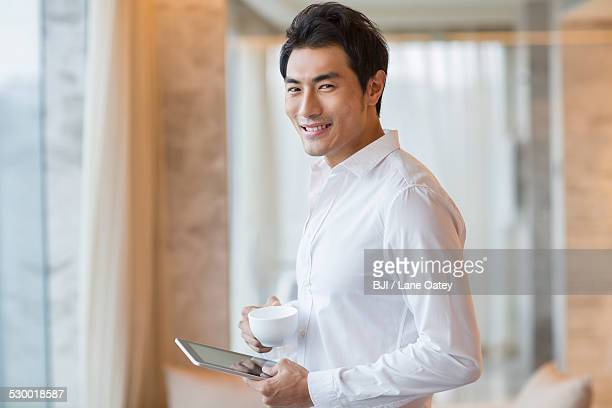 Young man drinking coffee with digital tablet