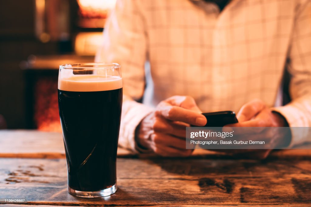 Young man drinking dark beer and using his smart phone in a pub : Stock Photo