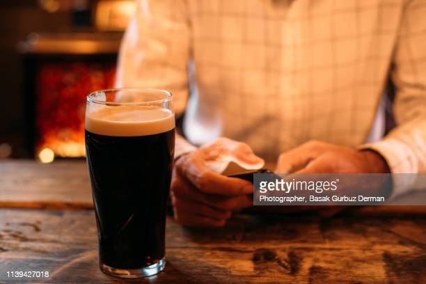 Young man drinking dark beer and using his smart phone in a pub