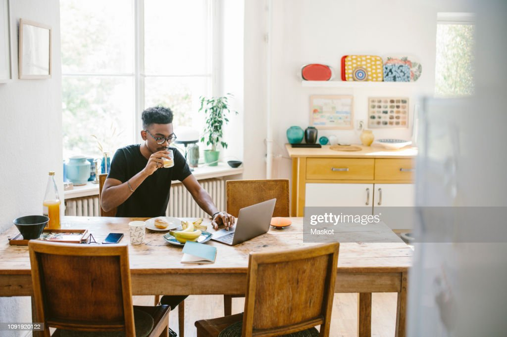 Young man drinking juice while using laptop at table in house : Stock Photo