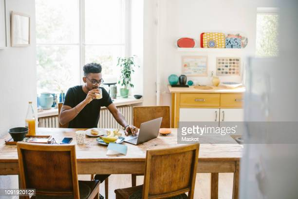 young man drinking juice while using laptop at table in house - homemaker stock pictures, royalty-free photos & images