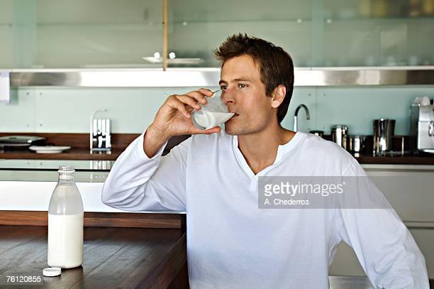 Young man drinking milk in kitchen