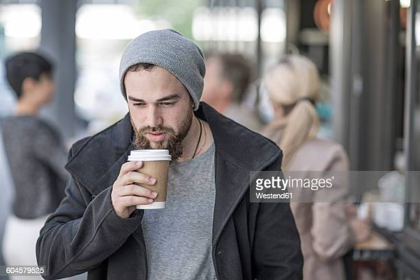 Young man drinking takeaway coffee in the city
