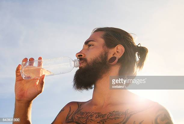 young man drinking water after excercise - lap body area stock photos and pictures