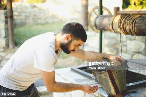 Junger Mann gut Trinkwasser aus zeichnen