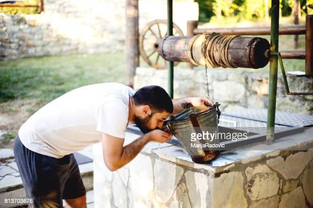 jonge man goed drinkwater uit trekken - putten stockfoto's en -beelden