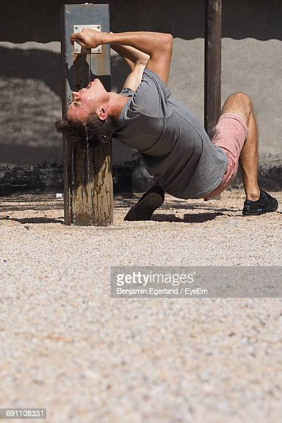 Young Man Drinking Water From Faucet On Street