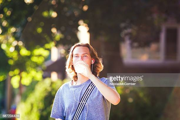Young man drinking water outdoors with earbuds on