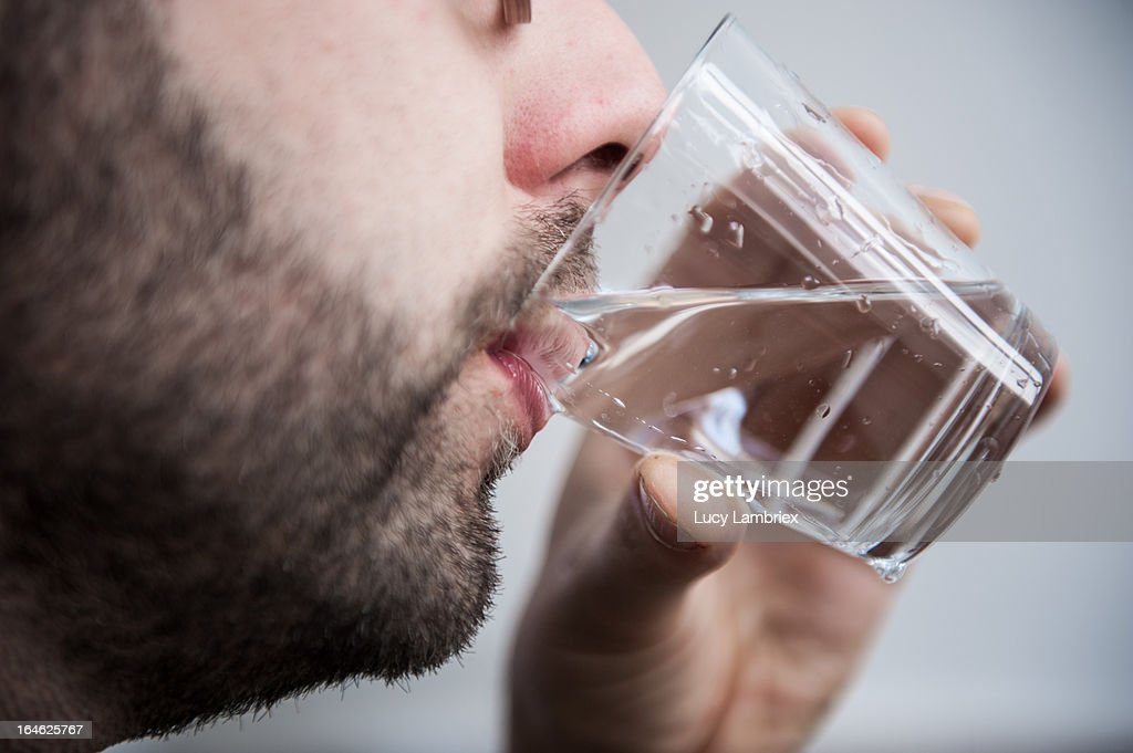 Young man drinking water : Stock Photo