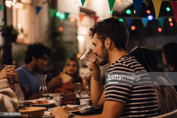 young man drinking water while having dinner with friends during garden party - woman sitting on man's lap stock pictures, royalty-free photos & images