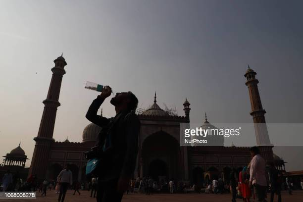 A young man drinks water from a bottle in the courtyard of Jama Masjid in the Old Quarters of Delhi