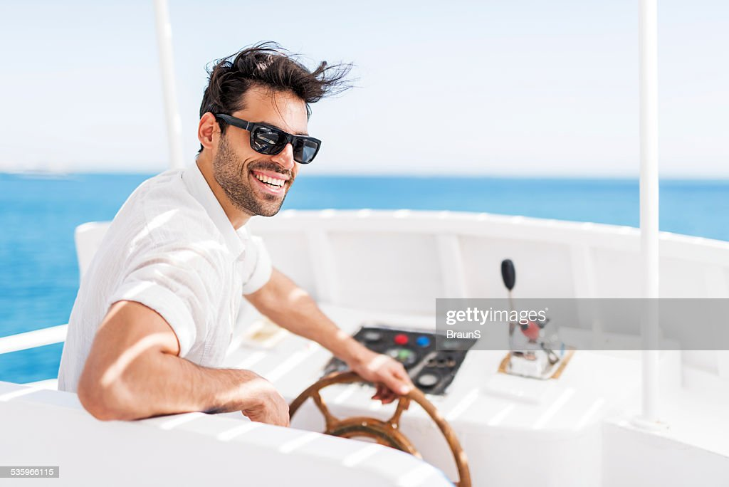 Young man driving a boat. : Stock Photo