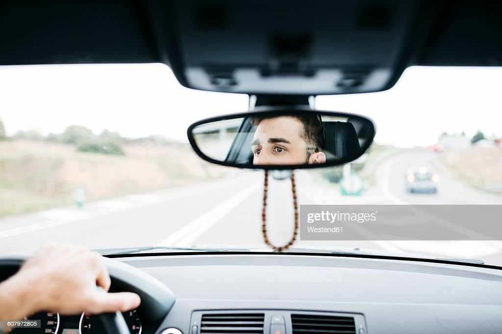 Young man driving a car, close up of rear mirror : Stock Photo