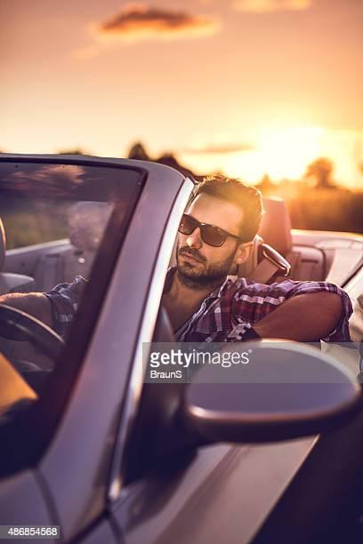 Young man driving a convertible car at sunset.