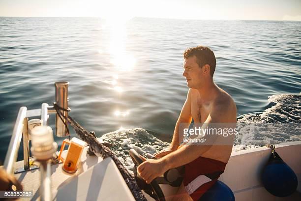 Young man driving a speedboat enjoying summertime