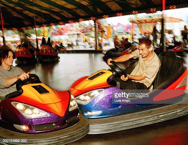 Young man driving bumper car into friend's car (blurred motion)