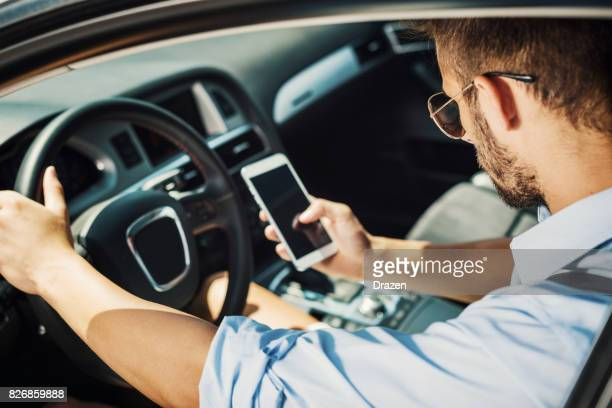 young man driving car for crowdsourced taxi - uber stock photos and pictures