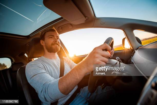 young man driving car on a sunny day - driving stock pictures, royalty-free photos & images