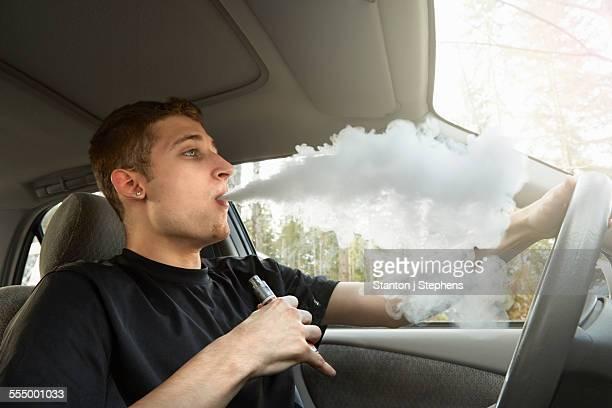 Young man driving car, smoking ecigarette