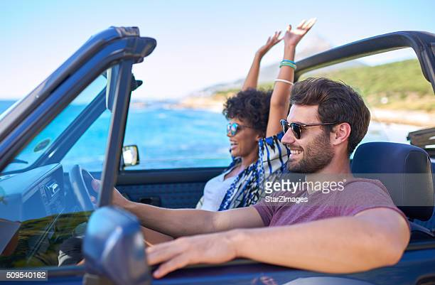 Young man driving car with his girlfriend in roadtrip