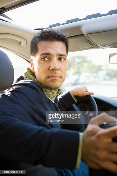Young man driving, looking over shoulder
