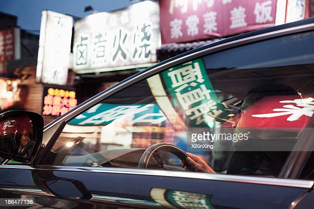 Young man driving through Beijing at night, illuminated store signs reflected off the windows of the car