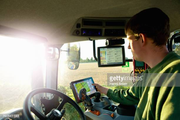 young man driving tractor using touchscreen on global positioning system - agriculture stock pictures, royalty-free photos & images