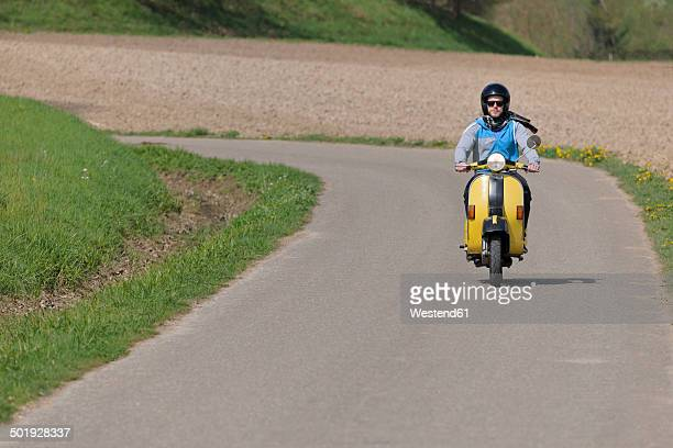 young man driving with his vespa on country road - one man only stock pictures, royalty-free photos & images