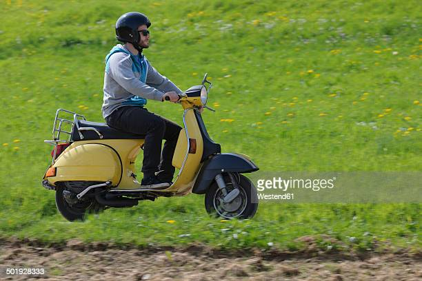 Young man driving with his Vespa on meadow