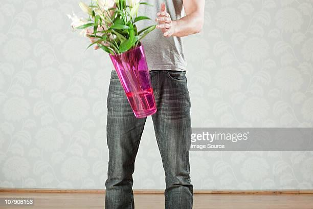 Junger Mann, über vase mit Blumen