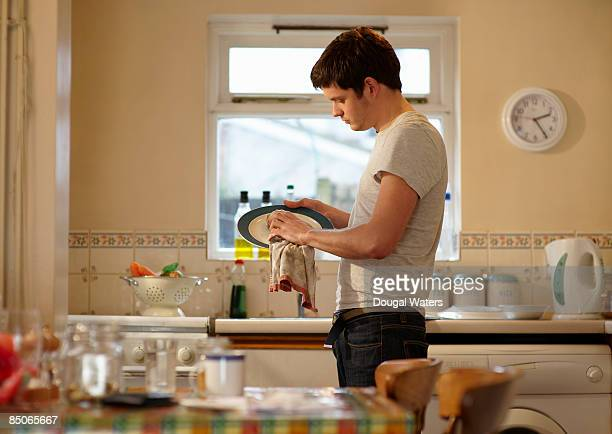 Young man drying plate in kitchen.