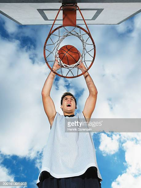 Young man dunking basketball in hoop, screaming, low angle view