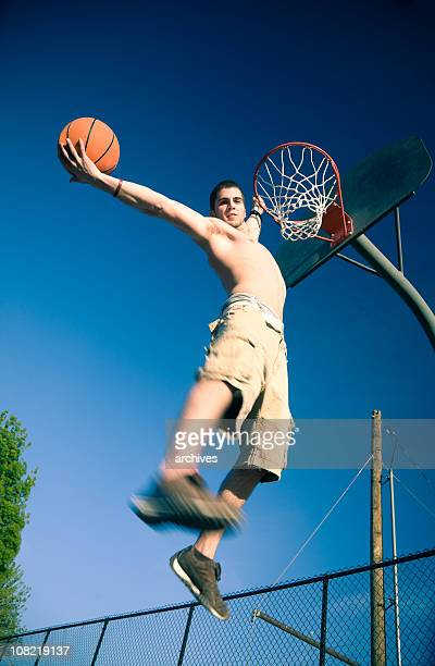 Young Man Dunking Basketball in Net on Court
