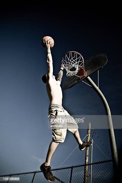 Young Man Dunking Basketball in Net on Street Court