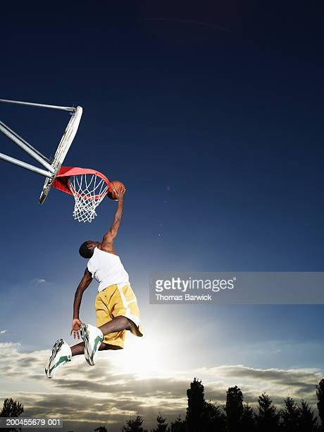 Young man dunking basketball outdoors at sunset, low angle view