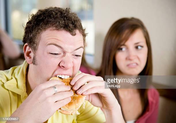 Young Man Eating a Cheeseburger