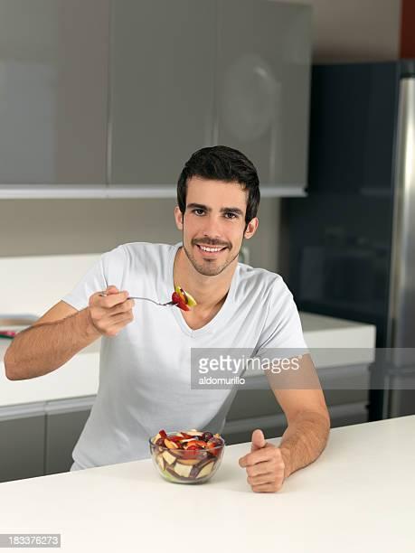 Young man eating a fruit salad