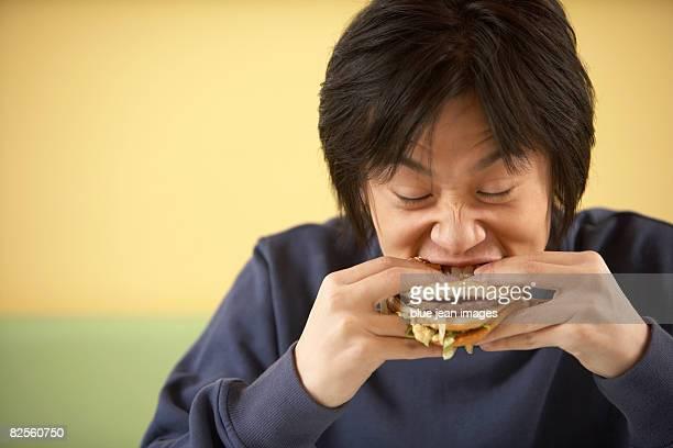 A young man eating a hamburger.