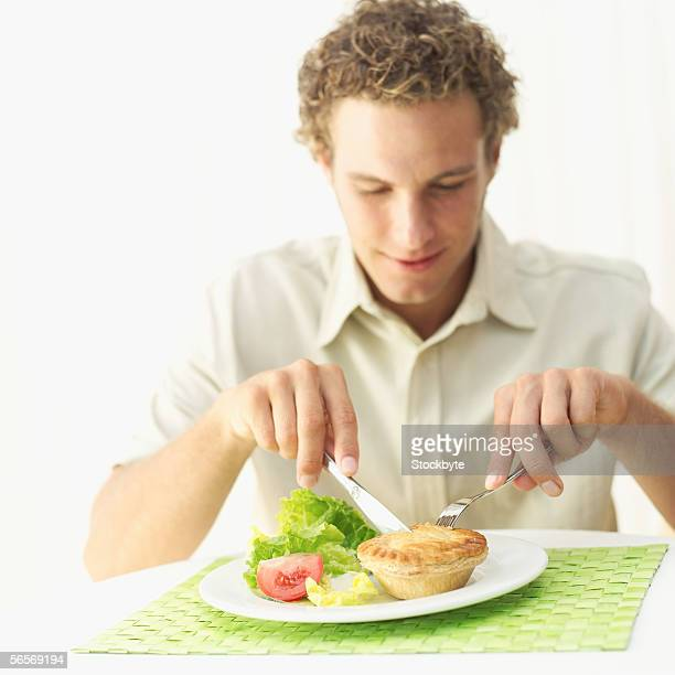 young man eating a pastry pie