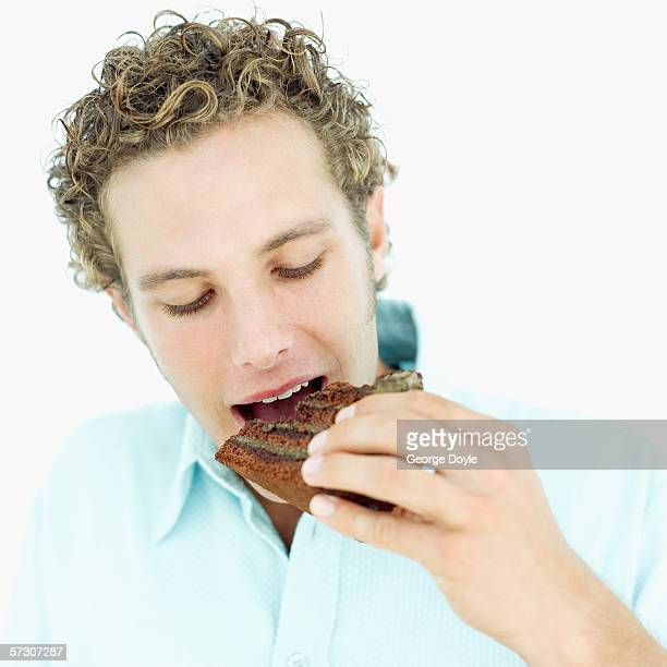 Young man eating a slice of chocolate cake