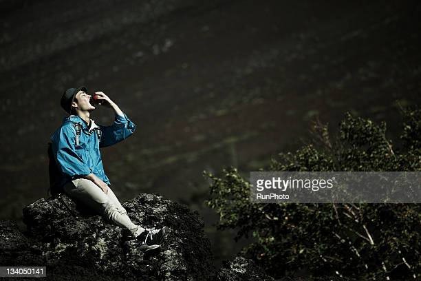 young man eating an apple at the mountain