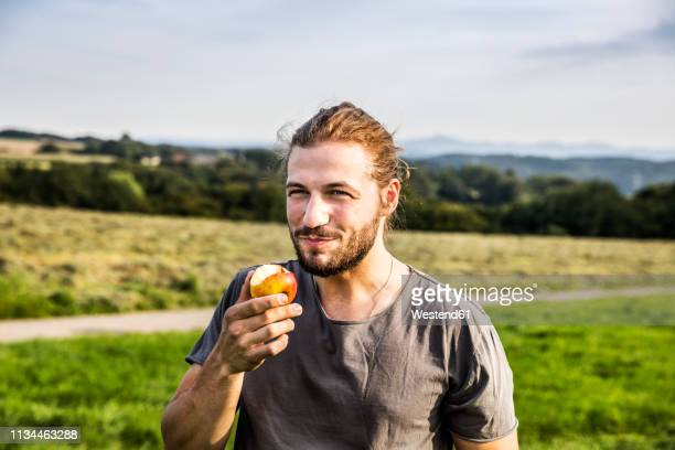 young man eating an apple in rural landscape - vergnügen stock-fotos und bilder