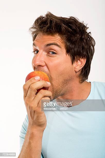 Young man eating apple, portrait, close-up