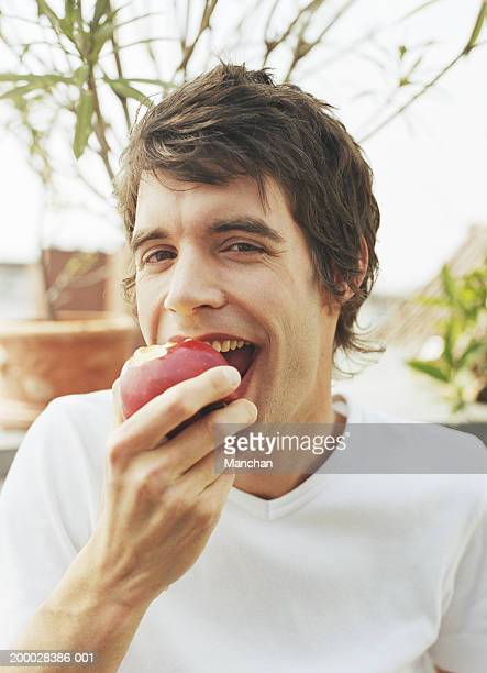 Young man eating apple, portrait