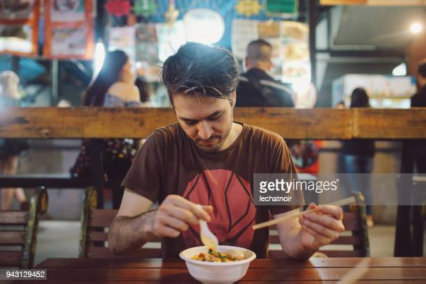 Young man eating authentic Thai food on a street market in Bangkok, Thailand