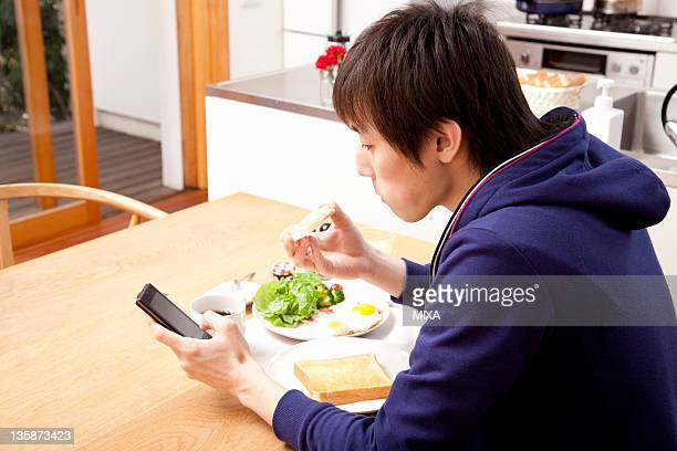Young man eating breakfast and checking Smartphone