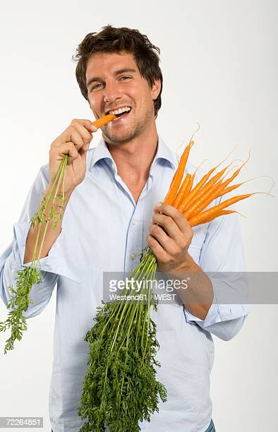 Young man eating carrot, close-up, portrait